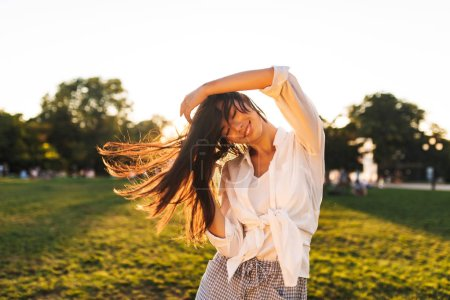 Beautiful smiling asian girl in white shirt happily dancing spending time in city park