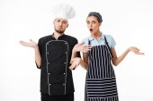 Young upset man chef in black uniform and white hat and woman cook in striped apron and cap amazedly looking in camera over white background