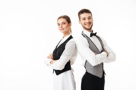 Foto de Joven sonriente camarero y camarera hermosa en camisas blancas y chalecos sstanding espalda con espalda feliz mirando en cámara con brazos doblado sobre fondo blanco - Imagen libre de derechos