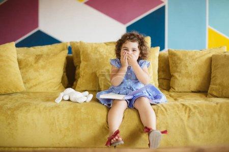 Photo pour Petite fille mignonne aux cheveux bouclés foncés en robe bleue avec livre enfant sur les genoux regardant joyeusement à la caméra couvrant la bouche avec les mains sur le canapé à la maison - image libre de droit