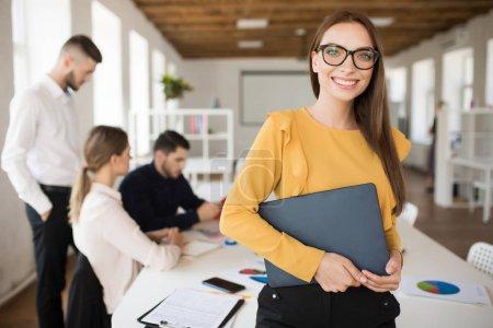 Photo pour Jeune femme d'affaires souriante dans les lunettes regardant joyeusement dans la caméra tenant le dossier dans les mains dans le bureau avec des collègues sur fond - image libre de droit