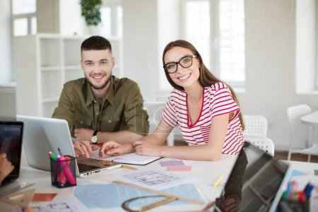 Young man and woman in striped t-shirt and eyeglasses happily looking in camera working together. Group of cool guys with laptop spending time in modern office