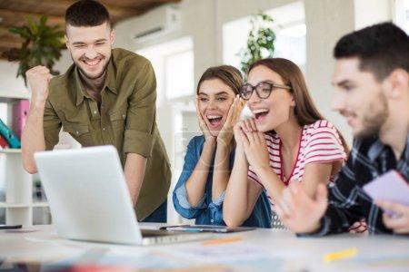Photo pour Jeunes gens d'affaires joyeux heureux de travailler sur ordinateur portable ensemble. Groupe d'hommes et de femmes souriants passer du temps dans un bureau confortable moderne - image libre de droit