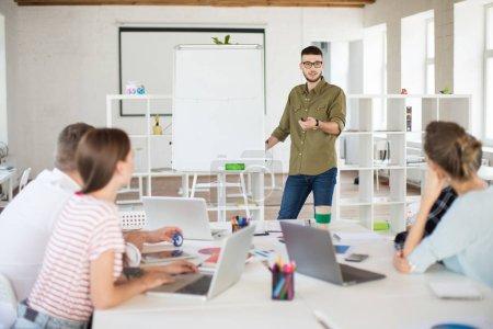 Photo pour Jeune homme en lunettes et chemise debout près de bord discuter du nouveau projet avec des collègues au travail. Groupe de personnes travaillant ensemble dans un bureau moderne - image libre de droit