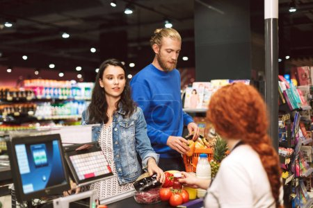 Young beautiful couple standing near cashier desk buying products together in modern supermarket
