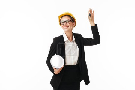 Photo for Young smiling pretty businesswoman in eyeglasses and yellow helmet happily looking in camera with plan and keys of new flat in hands over white background - Royalty Free Image
