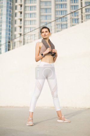 Young pretty woman in sporty top and white leggings holding little towel on shoulders dreamily looking aside over fuzzy background
