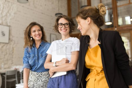 Three young cheerful women leaning on desk happily talking together spending time at work. Beautiful stylish girls working in modern office
