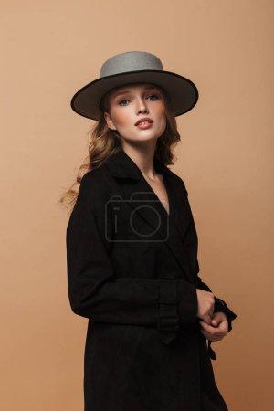 Photo pour Jeune femme attrayante avec des cheveux ondulés en manteau noir et chapeau regardant soigneusement à la caméra sur fond beige - image libre de droit