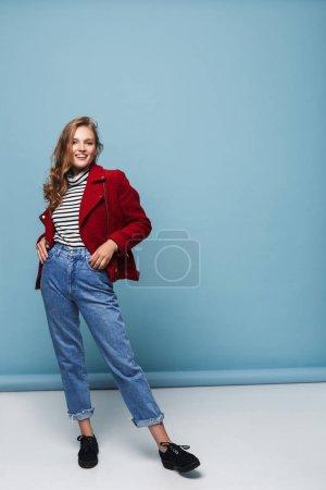 junge, glückliche Frau mit welligem Haar in roter Jacke und Jeans, die freudig in die Kamera blickt und Hände in Taschen über blauem Hintergrund hält