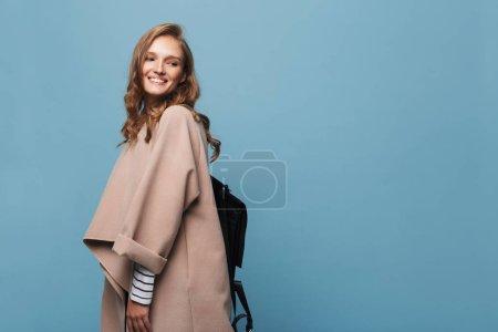 Foto de Hermosa niña sonriente con cabello ondulado en la capa de color beige con negro mochila alegremente mirando a un lado sobre fondo azul - Imagen libre de derechos