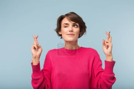 Photo for Young pretty woman with dark short hair in pink sweater keeping fingers crossed dreamily closing eye and biting lip over blue background - Royalty Free Image