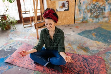 Photo for Young attractive smiling woman with closing eyes sitting on yoga mat in lotus pose and meditating happily spending time in big cozy workshop with wood easel and modern paintings on background - Royalty Free Image