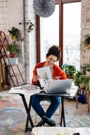 Photo pour Jeune femme souriante attrayante aux cheveux bouclés foncés assis à la table avec ordinateur portable et illustrations de mode dans les mains passer du temps dans un atelier incroyable avec une grande fenêtre sur le fond - image libre de droit