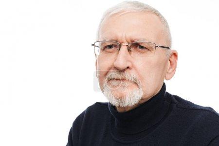 Photo pour Verticale de vieil homme beau avec le cheveu et la barbe gris dans des lunettes et le chandail noir regardant pensivement de côté au-dessus du fond blanc - image libre de droit