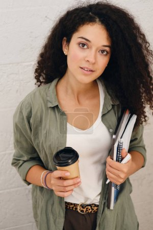 Photo for Young beautiful lady with dark curly hair in khaki shirt holding laptop with notepad and cup of coffee to go in hands dreamily looking in camera - Royalty Free Image
