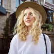 Portrait of attractive casual blond girl in hat dr...