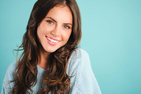 Portrait of gorgeous smiling girl in cozy sweater happily looking in camera over blue background