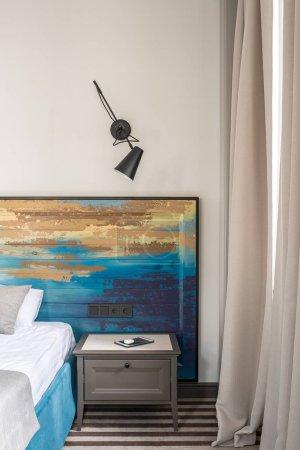 Photo pour Belle chambre d'hôtel avec un mur léger et un sol rayé. Il y a un lit bleu avec une tête de lit en bois coloré, table de chevet avec une tablette, lampe noire sur le mur, fenêtre avec des rideaux. Vertical . - image libre de droit