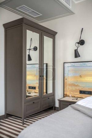 Photo pour Belle chambre d'hôtel avec des murs clairs et un sol rayé. Il y a un lit avec une tête de lit en bois coloré, une armoire gris foncé avec des miroirs, une table de chevet avec des accessoires, une lampe noire sur le mur. Vertical . - image libre de droit