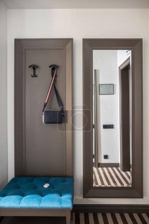 Photo pour Hall dans une chambre d'hôtel avec des murs clairs et un sol rayé. Il y a un support bleu, miroir pleine longueur, cintres avec un sac à bandoulière suspendu. Vertical . - image libre de droit