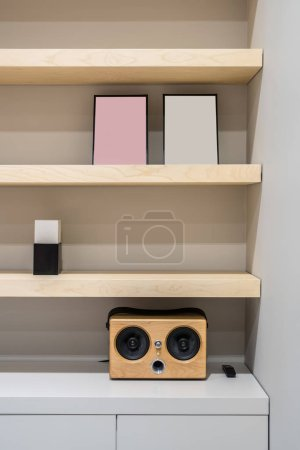 Photo for Light wooden shelves on the gray wall background in a luminous office. There is a speaker with a black remote controller, frames, lockers. Closeup. Vertical. - Royalty Free Image