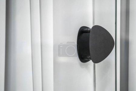 Black handle on glass door in luminous interior