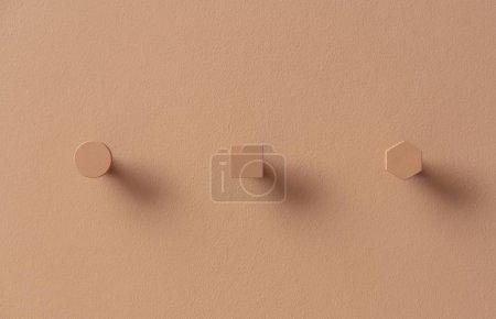 Photo pour Cintres géométriques métal orange tendance sur le même mur texturé de couleur à l'intérieur. Elles sont rondes, carrées et hexagonales. Photo horizontale rapprochée . - image libre de droit