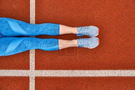 Photo pour Les jambes des filles en pantalon bleu et baskets grises sont couchées sur le stade rouge avec des lignes blanches à l'extérieur. Gros plan vue de dessus photo. Horizontal . - image libre de droit