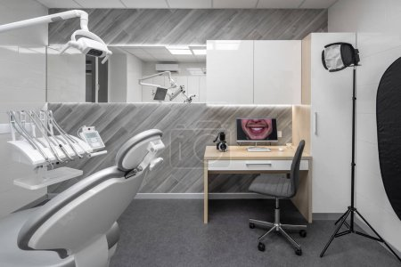 Photo pour Cabinet dans une clinique dentaire avec des murs clairs et un sol gris foncé. Il y a un lieu de travail avec chaise et équipement dentaire, table avec ordinateur et appareil photo, miroir large, lampe de poche, casiers, lampes lumineuses . - image libre de droit