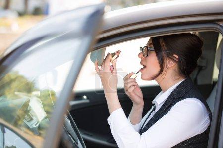 Photo pour Plus grand modèle peint ses lèvres alors qu'elle est assise au volant de sa propre voiture - image libre de droit