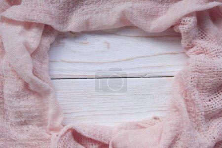 Photo pour Foulard rose formant un cadre sur un fond en bois blanc, mise au point sélective sur le tissu (espace de copie au centre pour votre texte ) - image libre de droit