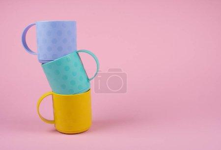 Photo pour Empilement de tasses bleues, vertes et jaunes sur fond rose pastel (concept minimalisme), espace de copie à droite pour votre texte - image libre de droit