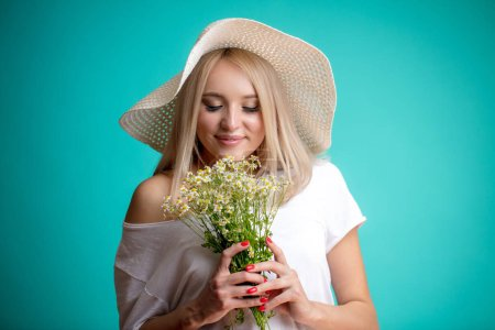 beautiful girl smelling white flowers with closed eyes