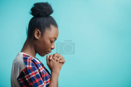 close up side view portrait of black girl with lively faith. expiatory faith.
