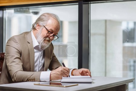 close up side view image of old office worker scribbling away in notebook