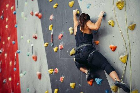 Photo pour Une jeune femme sportive s'entraîne dans un gymnase d'escalade coloré. Gratuit grimpeur fille grimper à l'intérieur - image libre de droit
