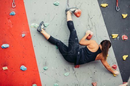 Beautiful young woman taking a big step up an artificial wall
