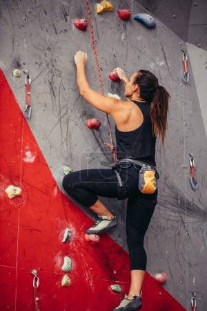 Young woman doing professional bouldering in climbing gym indoors