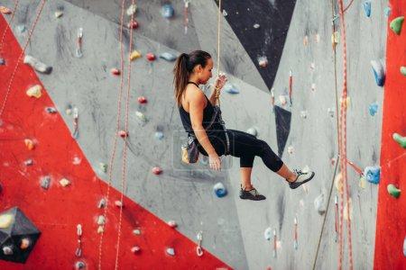 Photo pour Attrayant womanchoosingn sportif un mur coloré artificiel avec poignées et crochets . - image libre de droit