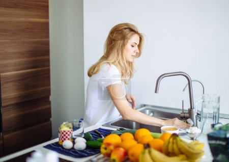 Young woman cleans dishware in kitchen