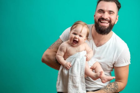 Photo for Young happy bearded father in white t-short holding his laughing infant daughter wrapped in towel in arms, studio shot on blue background with copyspace. - Royalty Free Image