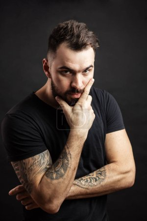 Photo for Portrait of a handsome beared strong man with muscular tattooed hands keeping crossed looking at camera over back background. Health, Sport, Mans Beauty Concept - Royalty Free Image