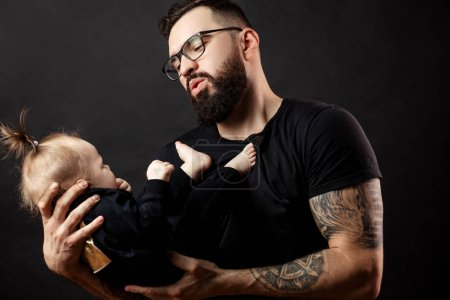 handsome father holding his cute newborn baby