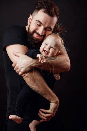 Loving father embracing gently his lovely funny infant girl, closing his eyes from delight, tenderness and love, isolated studio shot over black background.