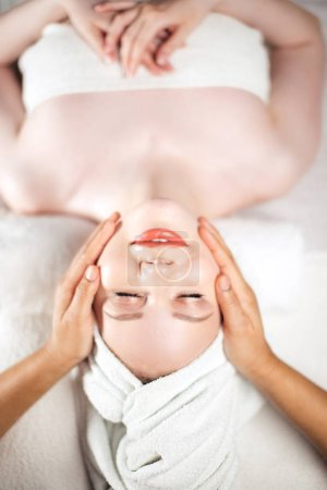 Photo for Skin And Body Care. Close-up of caucasian pretty female getting face lifting massage in luxury spa salon. Cosmetological Face Massage. Facial Beauty Treatment. Hotel Spa Zone - Royalty Free Image
