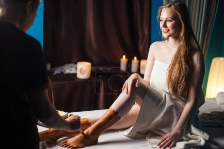 Photo for Young woman getting spa treatment in healthcare clinic. Beautiful girl with loose long blonde hair having clay body mask applied by beautician. Mud therapy. - Royalty Free Image
