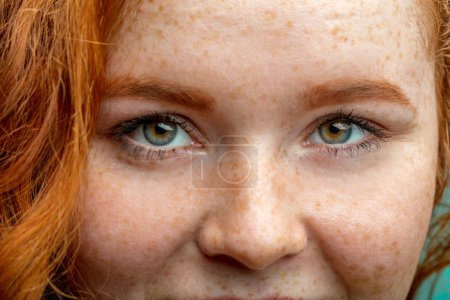 Close up macro face of young red ginger freckled woman with beautiful green eyes