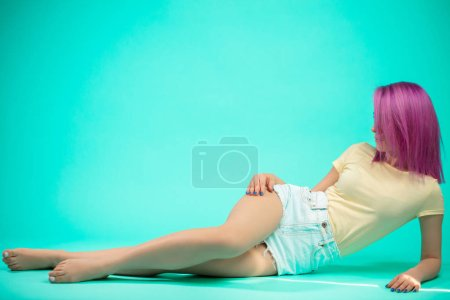 Young woman sitting on the floor isolated