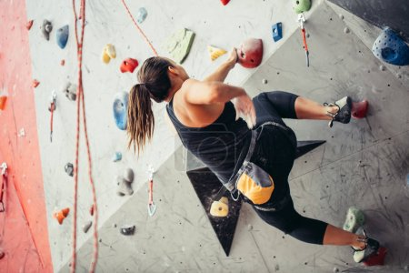 Climber young woman climbing on practical wall indoor, bouldering, recreation, sport